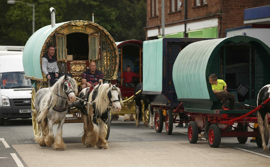Travellers drive their traditional Romany caravans along the main road in Appleby in Westmorland